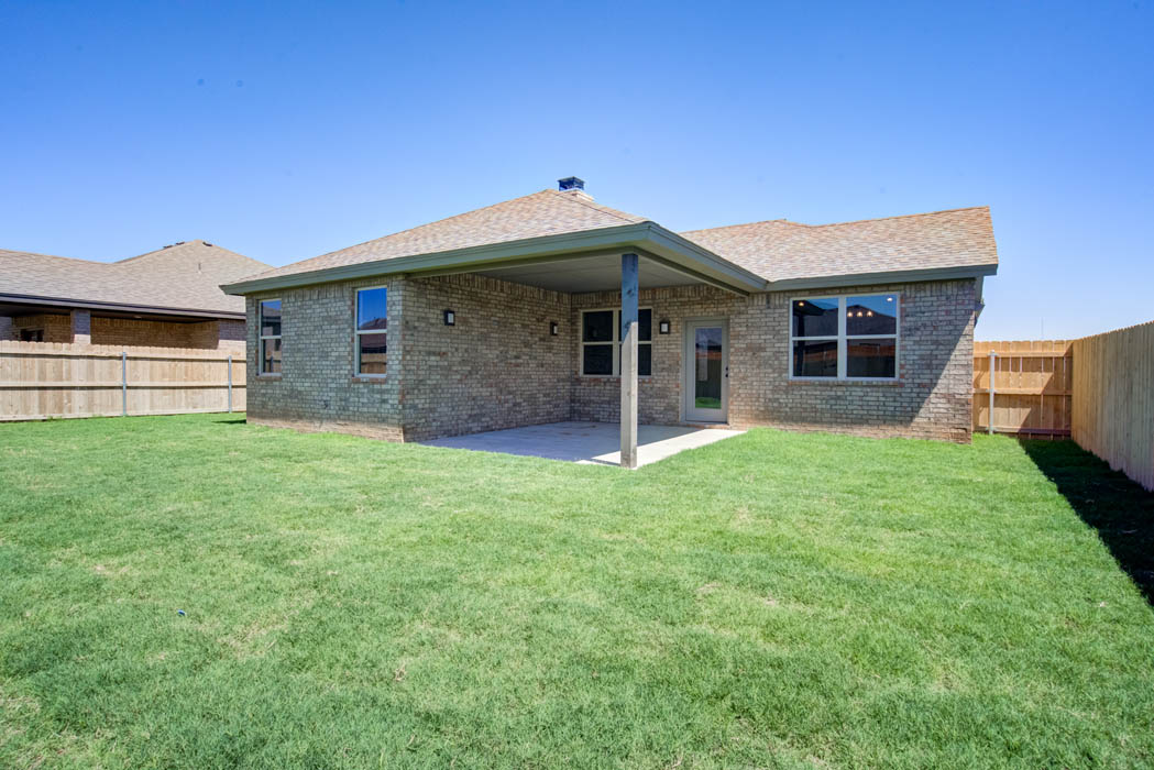 View of backyard patio and spacious yard in Lubbock home for sale.