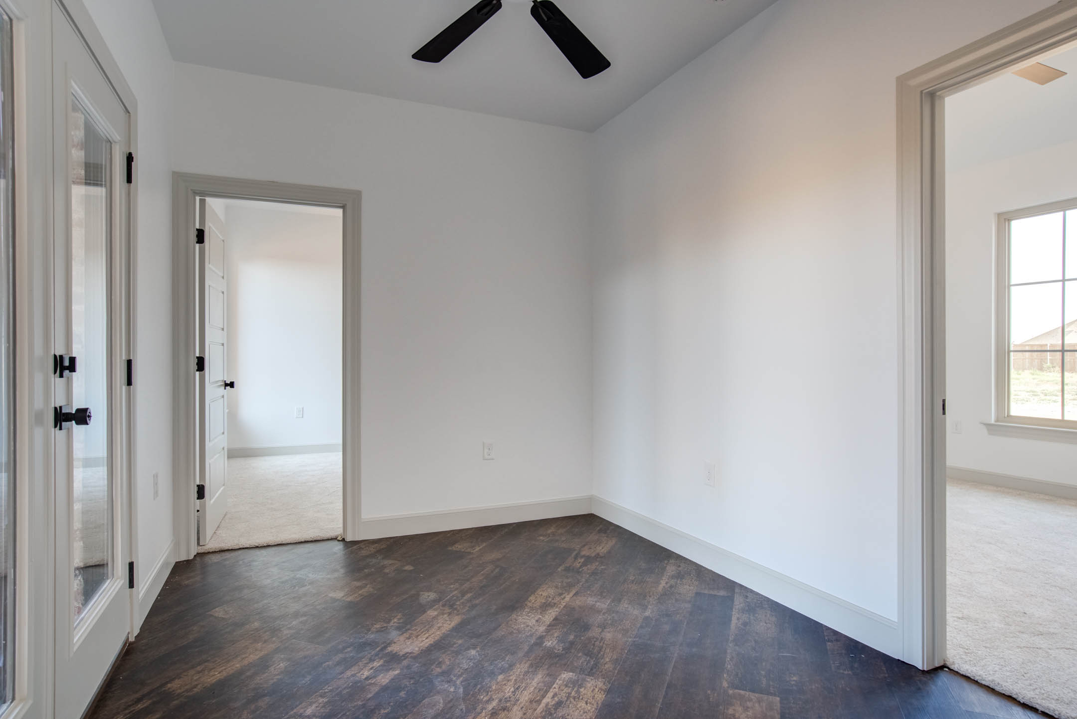 Spacious intersecting hallway for bedrooms to see out to patio in new home for sale.