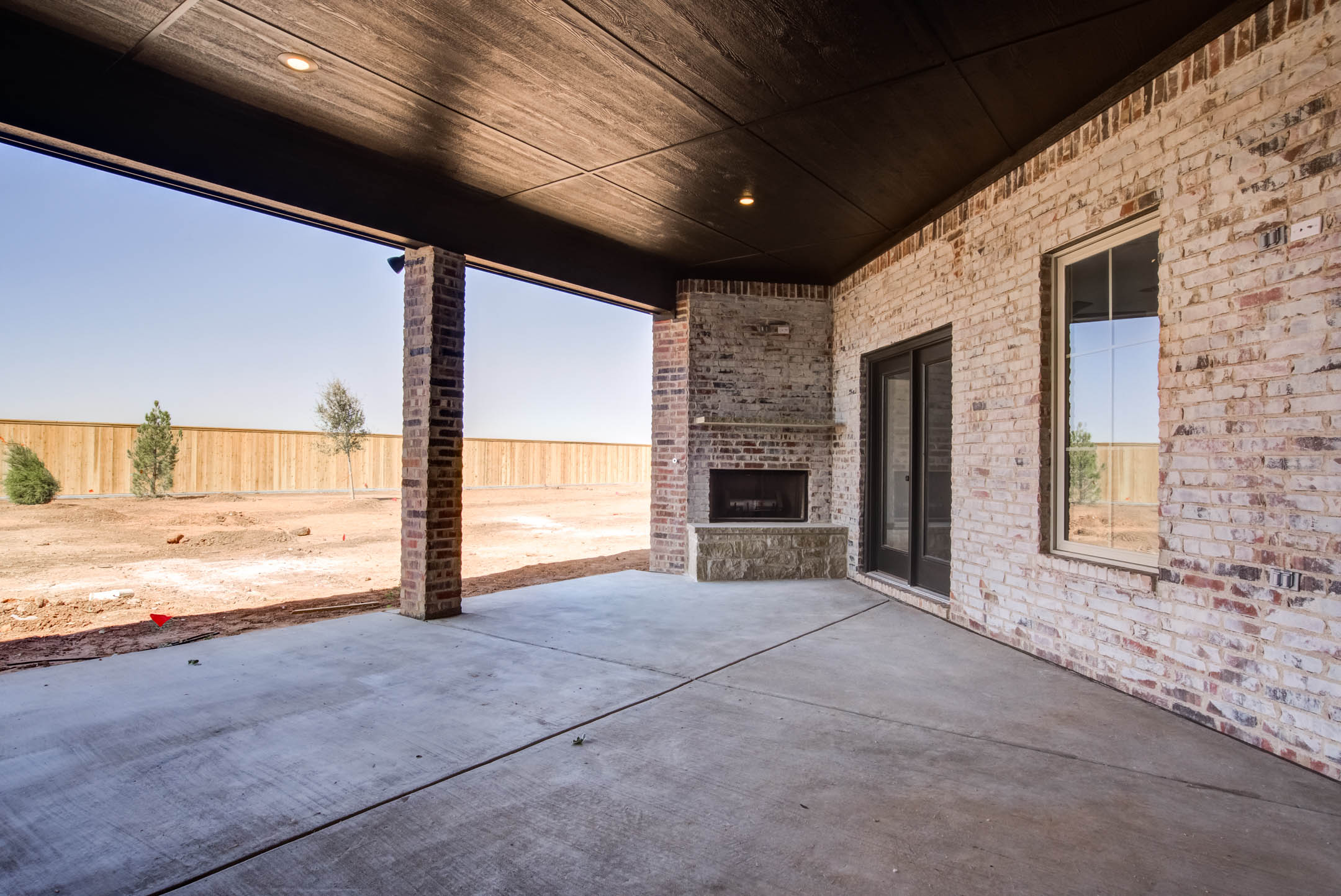 Long view of spacious covered patio and large backyard, as part of a new home for sale near Lubbock.