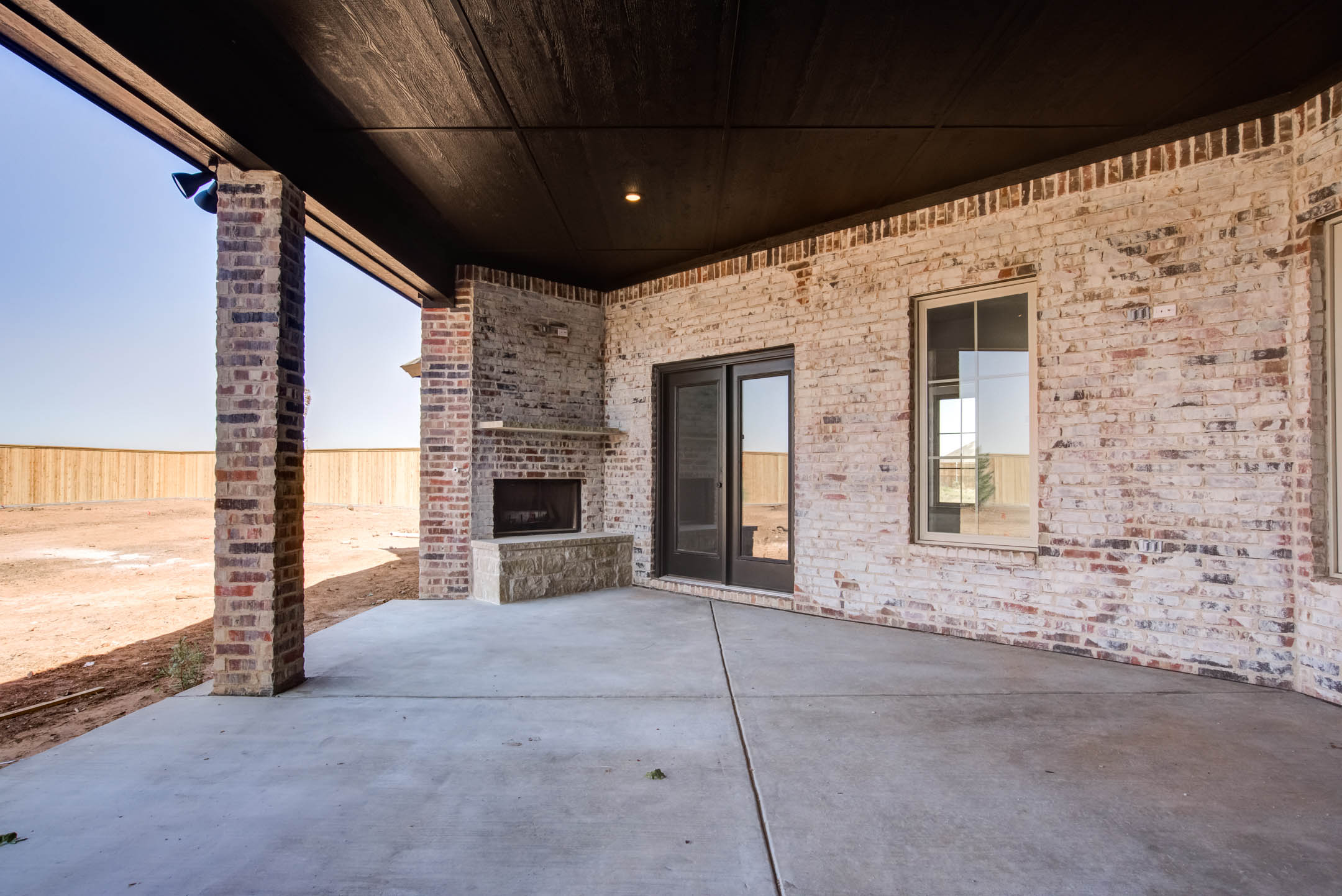Long view of spacious covered patio with fireplace, part of a new home for sale near Lubbock.