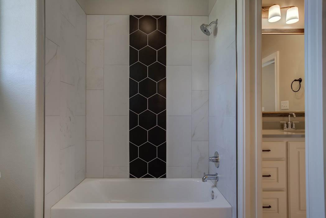 Tile detail in tub shower of guest bathroom.