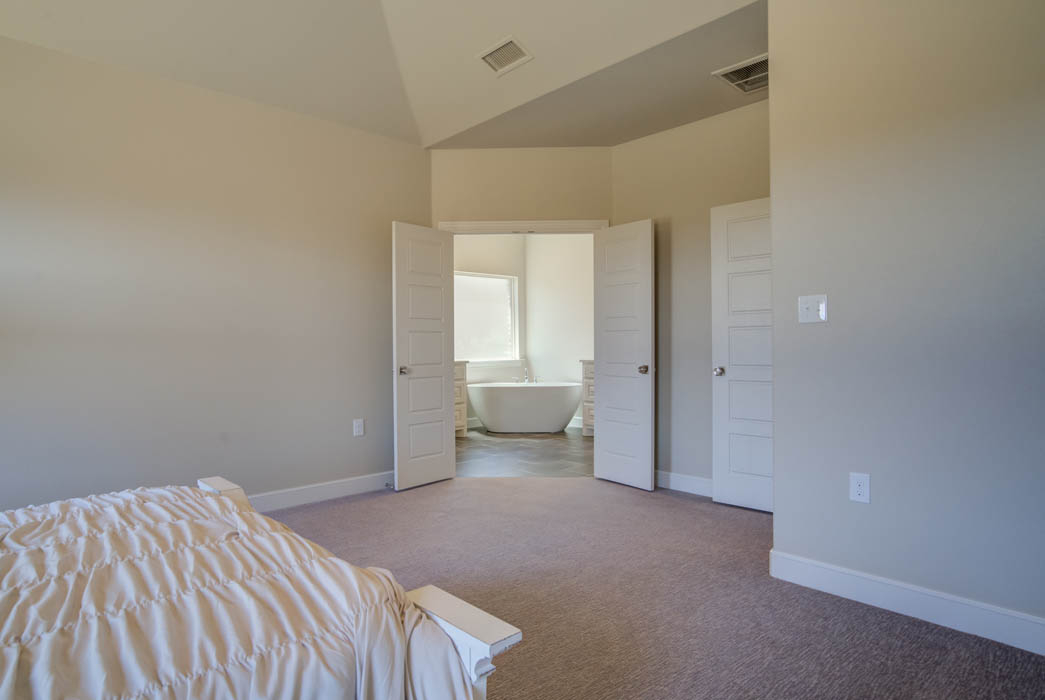 Master bedroom with double-door treatment in new home in Wolfforth, Texas.
