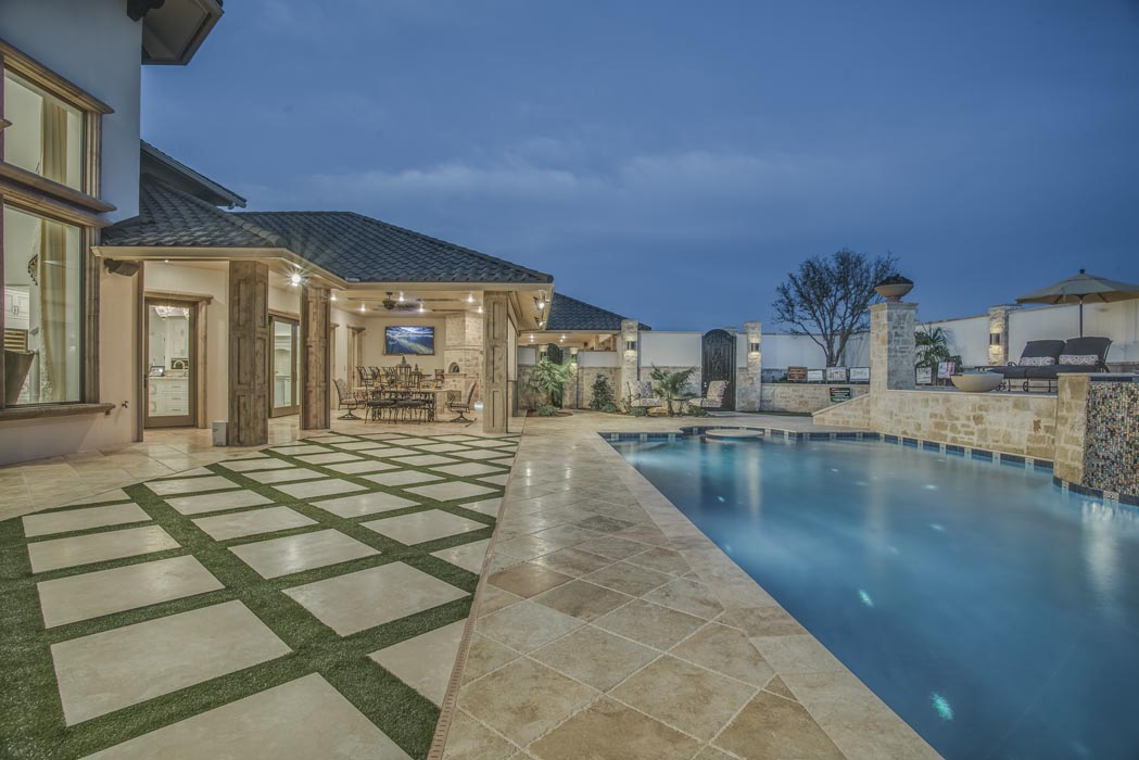Evening view of pool and specialty ground stonework, on grounds of custom home in Lubbock.