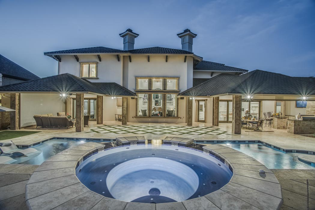 Evening view of overflow hot tub of custom home in Lubbock.
