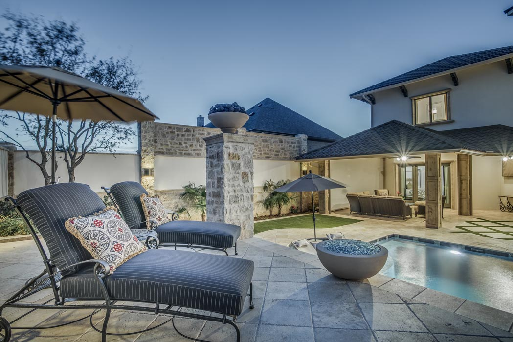 Evening view of lounging area near pool on grounds of custom home in Lubbock.