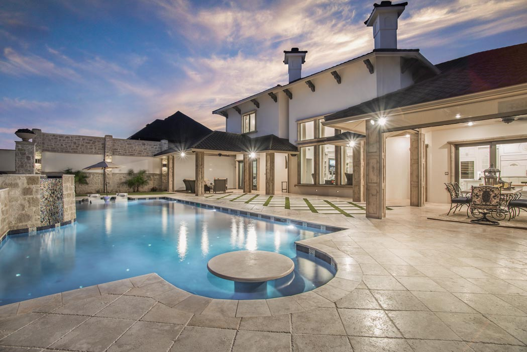 Evening view of pool and spacious patio on grounds of custom home in Lubbock.