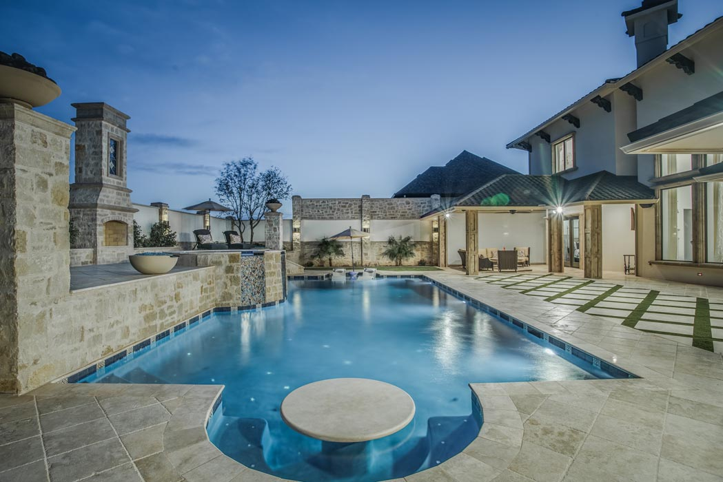 Evening view of lighted pool of custom home in Lubbock.