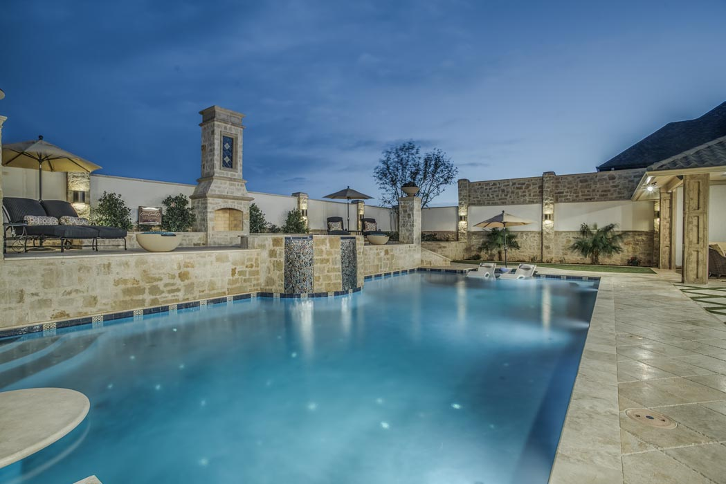 Evening view of pool and adjacent fireplace feature, on grounds of custom home in Lubbock.