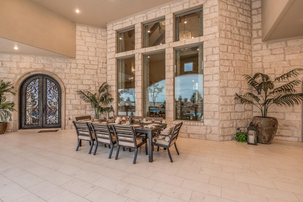 Large outdoor living space, directly in front of tall windows looking out from living area.