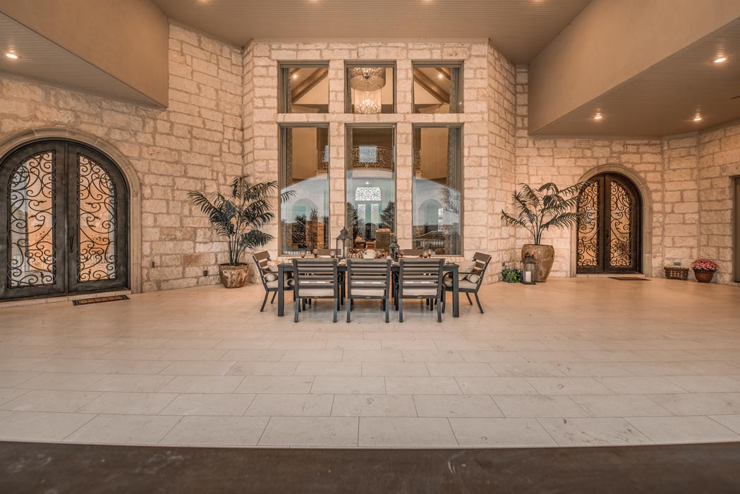 Spacious outdoor patio of custom home featuring special curved exterior doors.