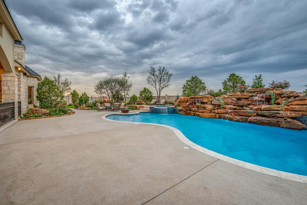 Long view of pool and patio area in outdoor space, part of a custom Lubbock home.