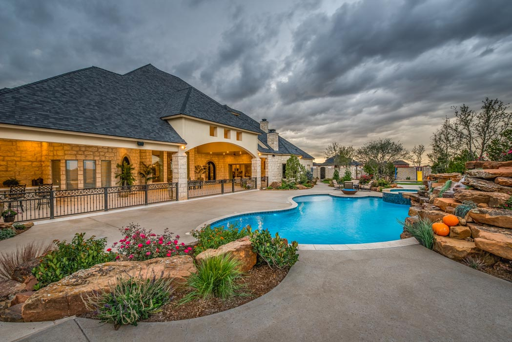 View of pool with waterfall, with custom Lubbock home in the background.