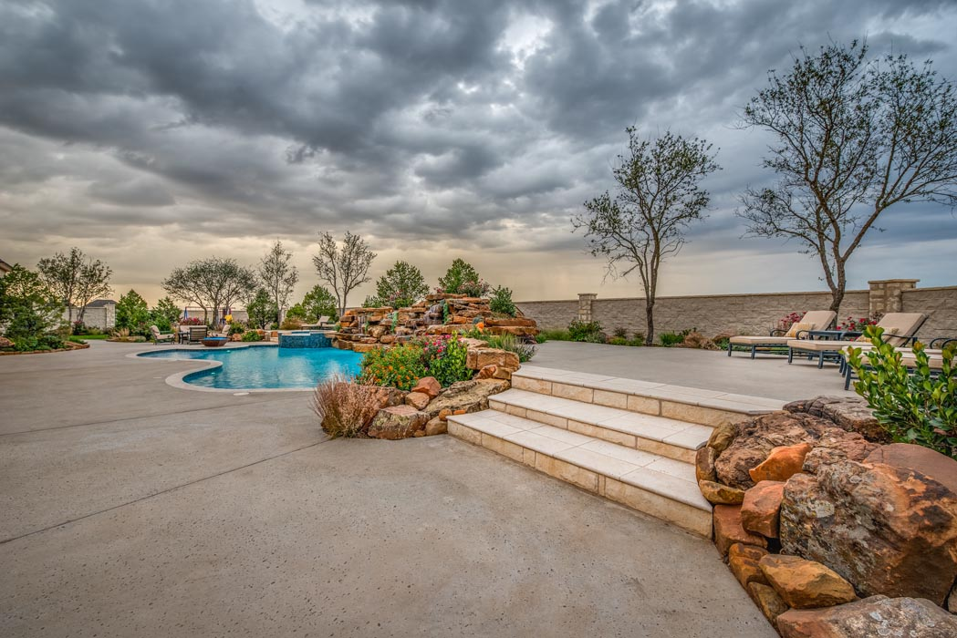 View of flowing steps on spacious patio area near pool of a custom home in Lubbock.