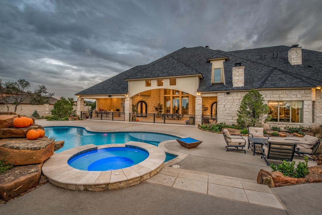 View of outdoor living space with pool and custom home, in the Lubbock, Texas area.