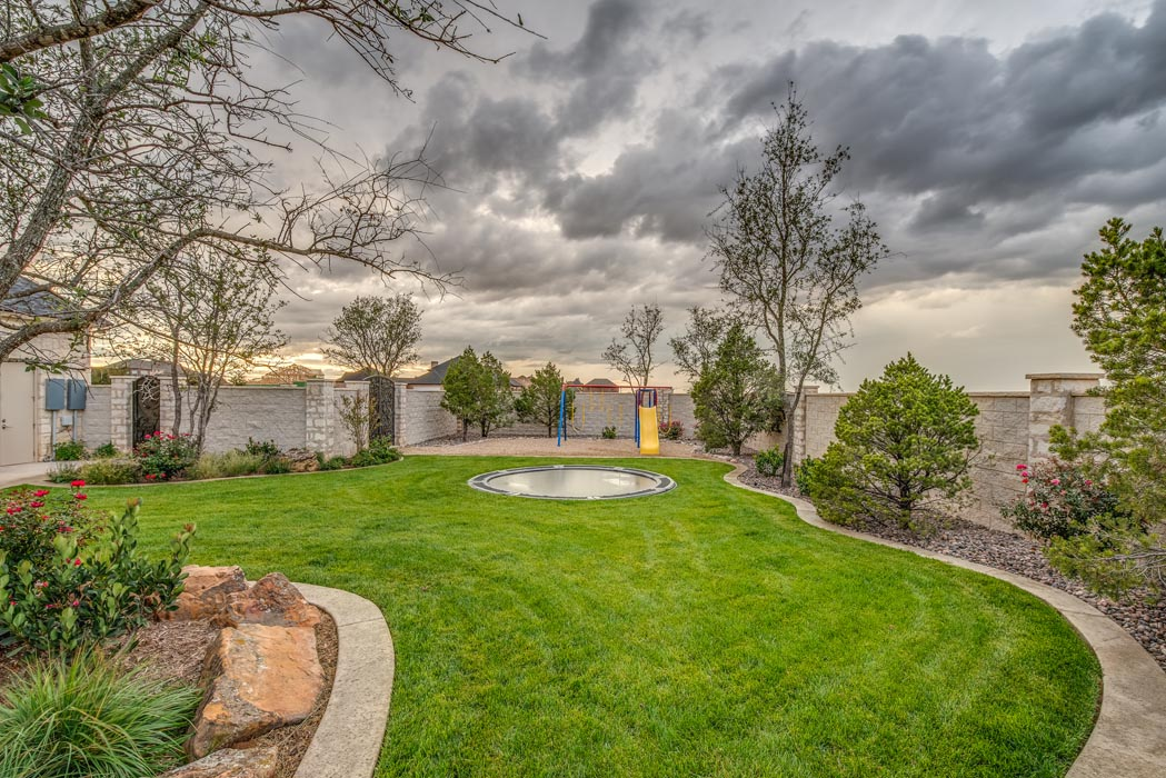 Beautiful spanse of green space in outdoor living area of custom home in West Texas.