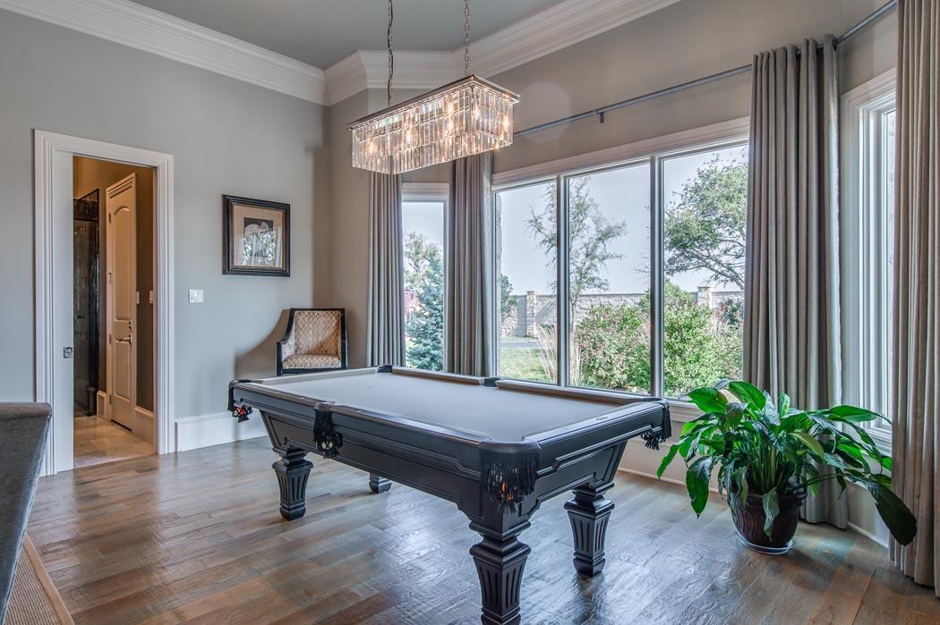 Billiard table in area adjacent to living room in custom home in Lubbock.