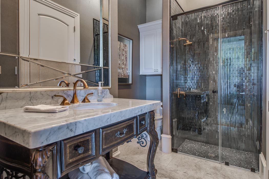 Amazing custom bath in custom home, with glass shower and black tile.