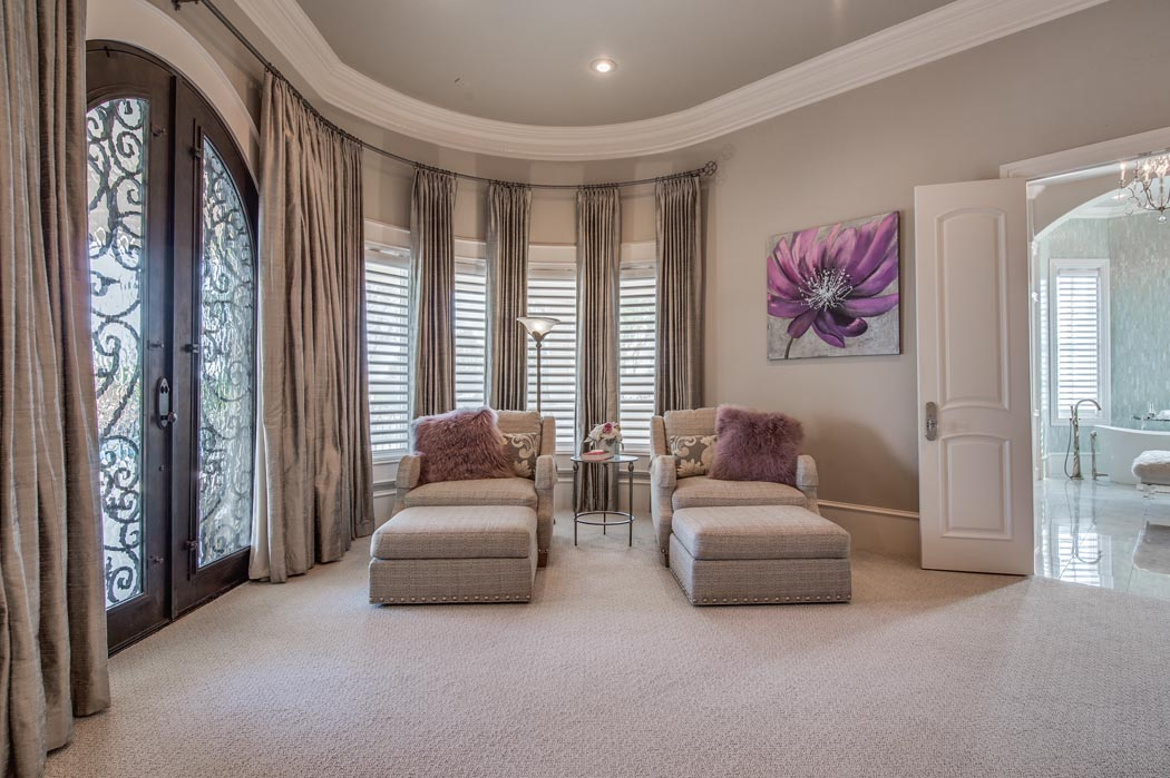 Spacious master bedroom with curved wall and plenty of windows.
