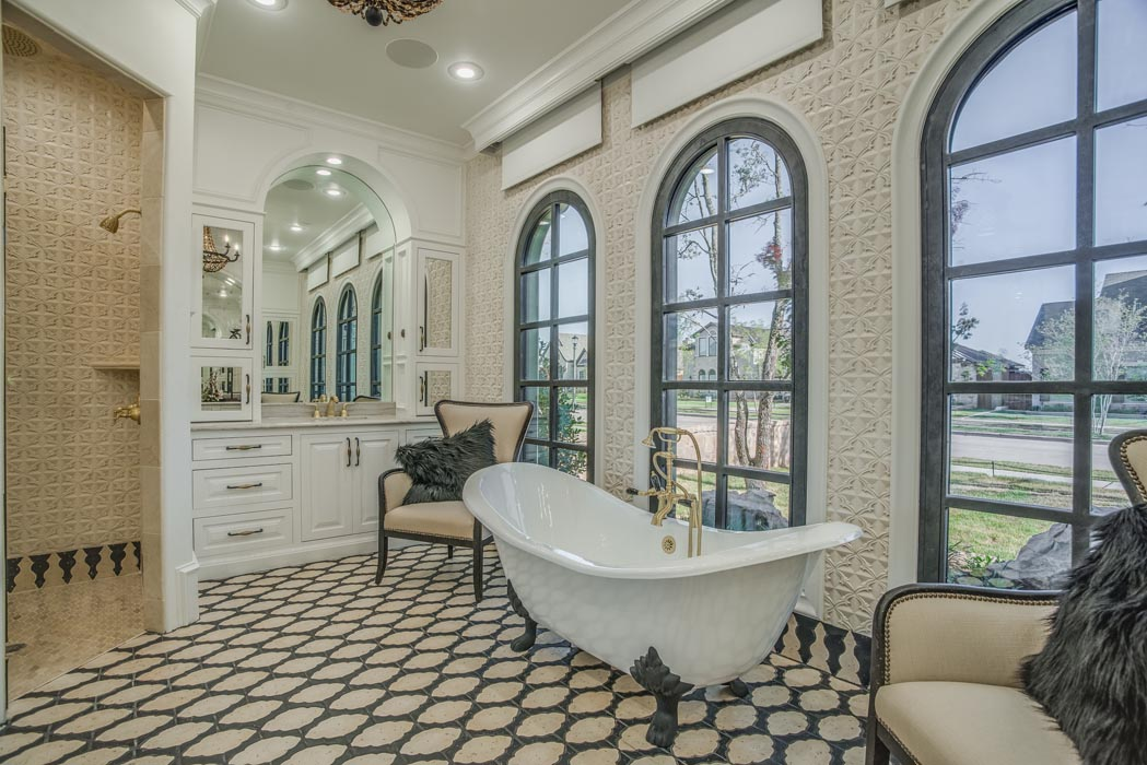 Master bath with tub and arched windows.
