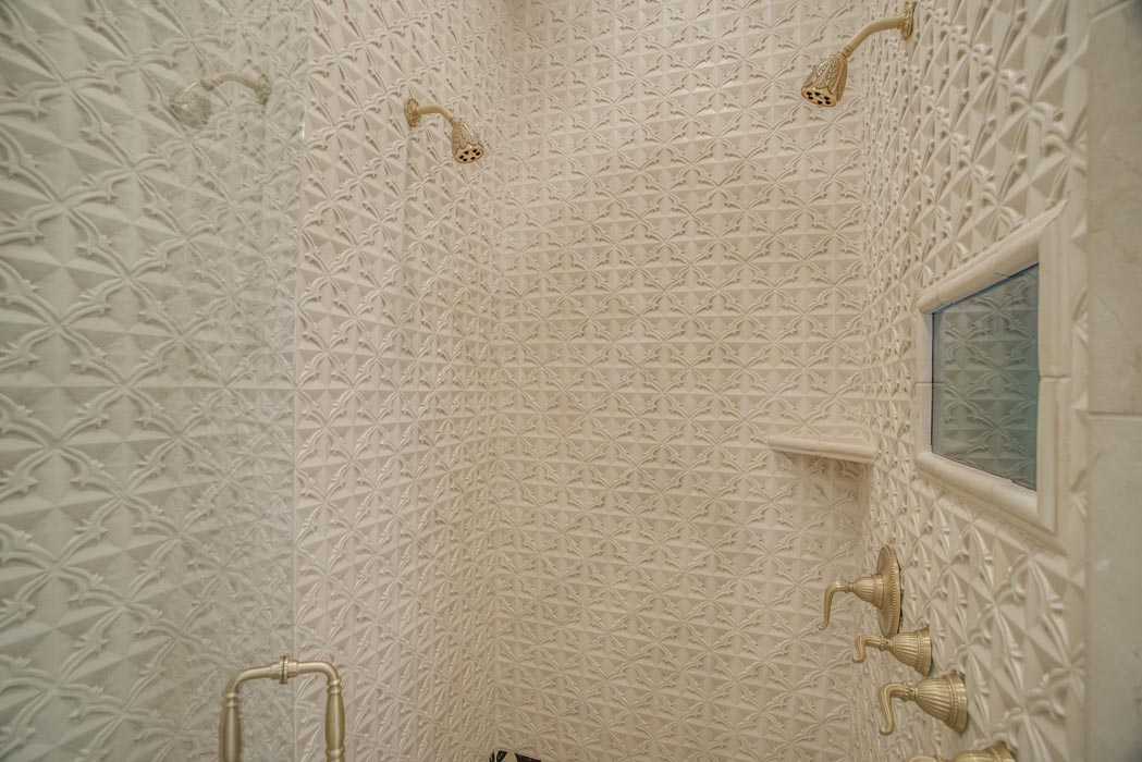 Custom shower with specialty tile and double shower heads in custom home.