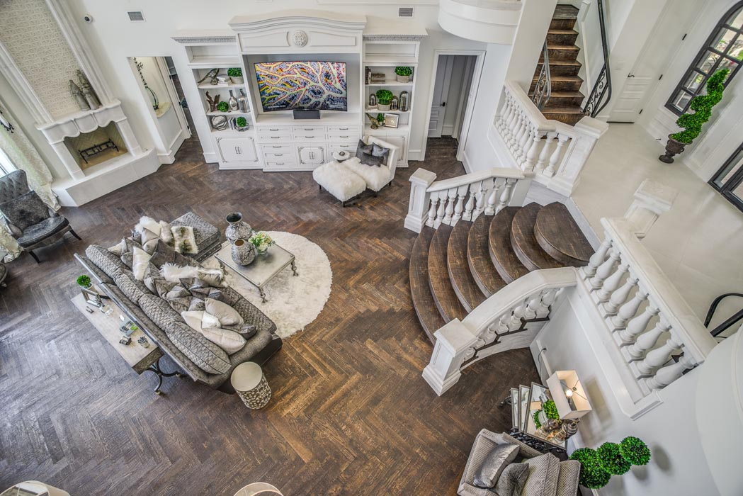 View from second story landing into large living area of custom home.