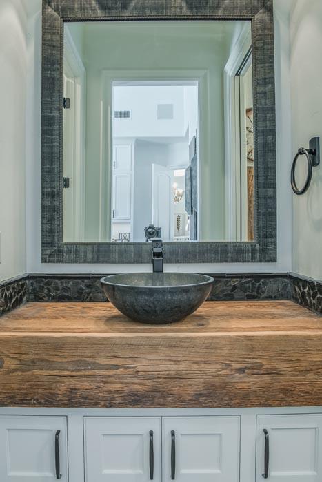 Bath in custom home, featuring wood vanity and bowl sink.