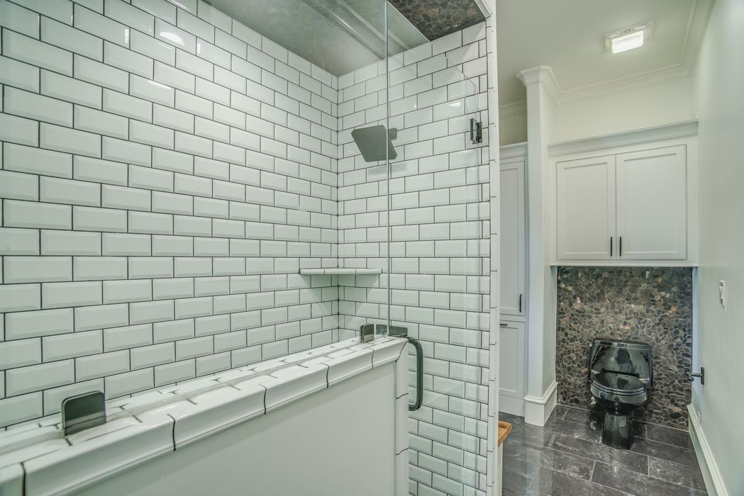 Water closet and roomy shower of bath in custom home.