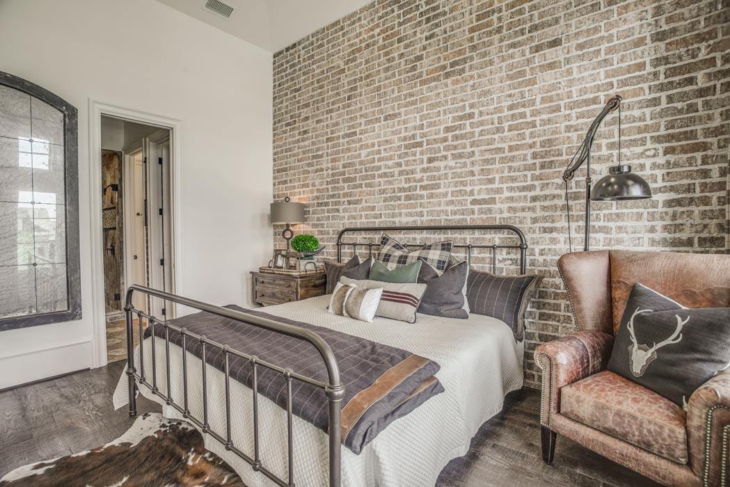 Bedroom with brick accent wall in custom home.