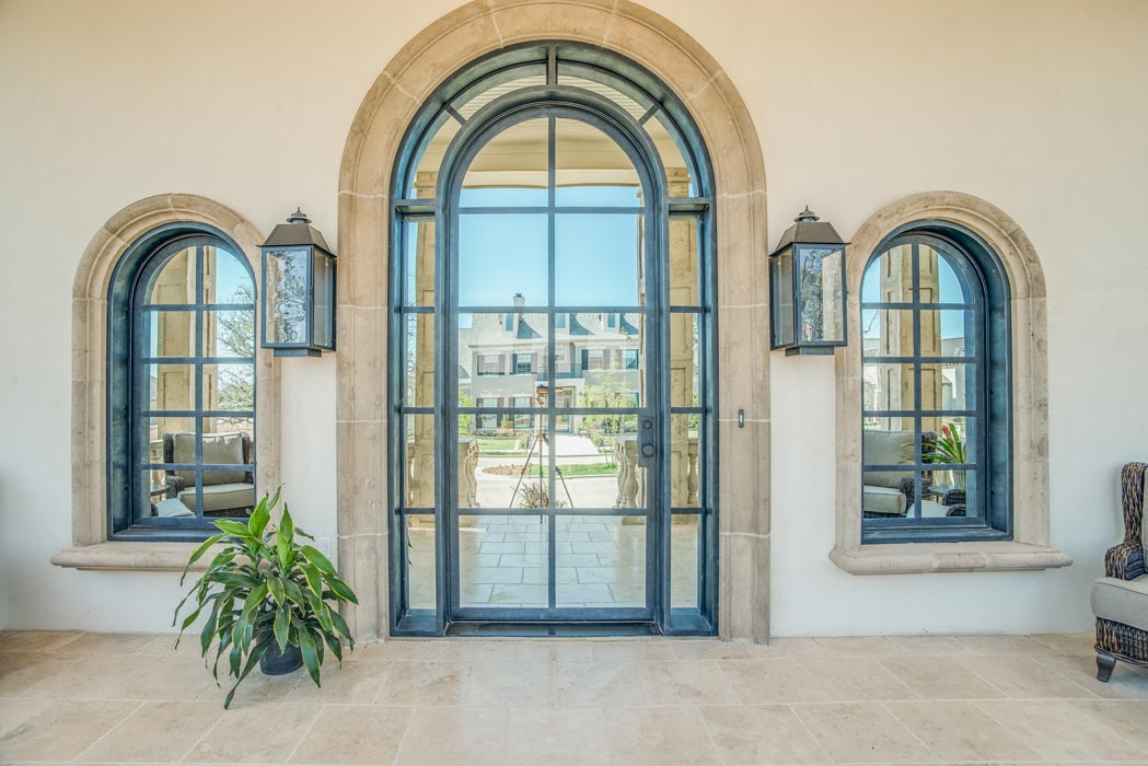 Outdoor patio area of custom home, featuring arched door and windows.
