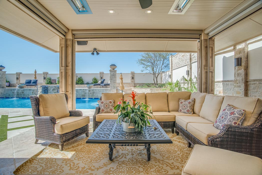 Spacious covered patio seating area in elegant lawn area of custom home.