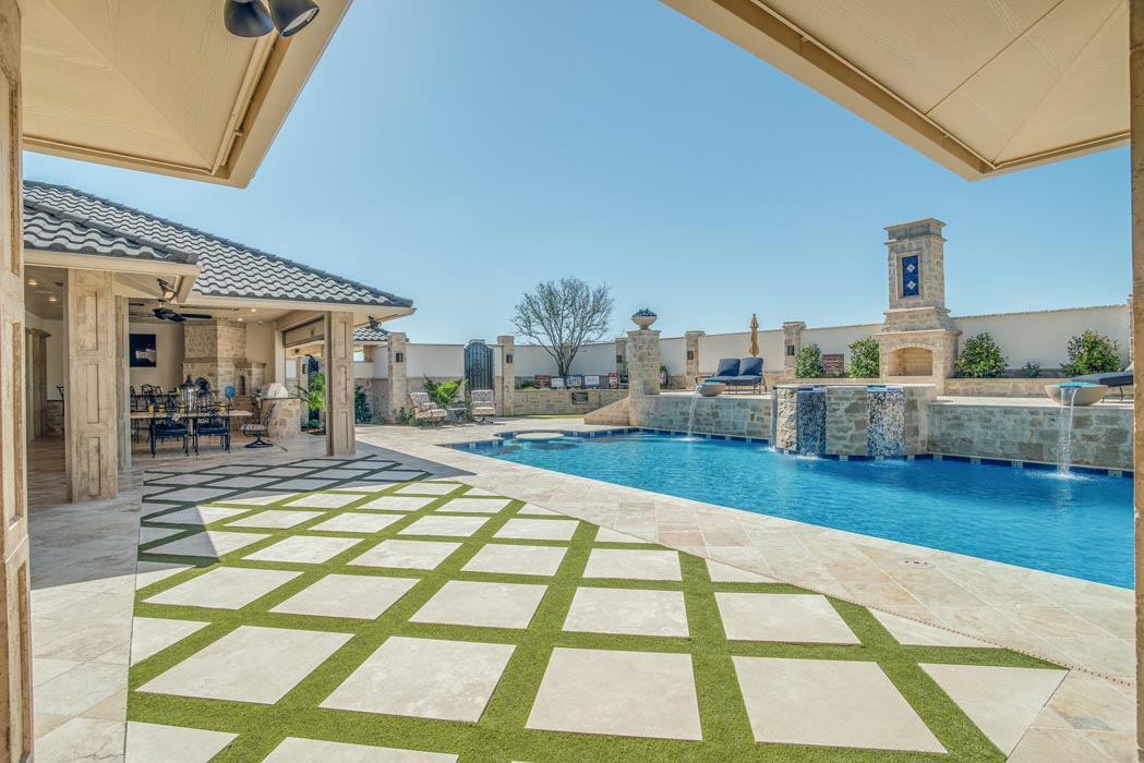 Elegant paved area of patio leading to pool in custom home.