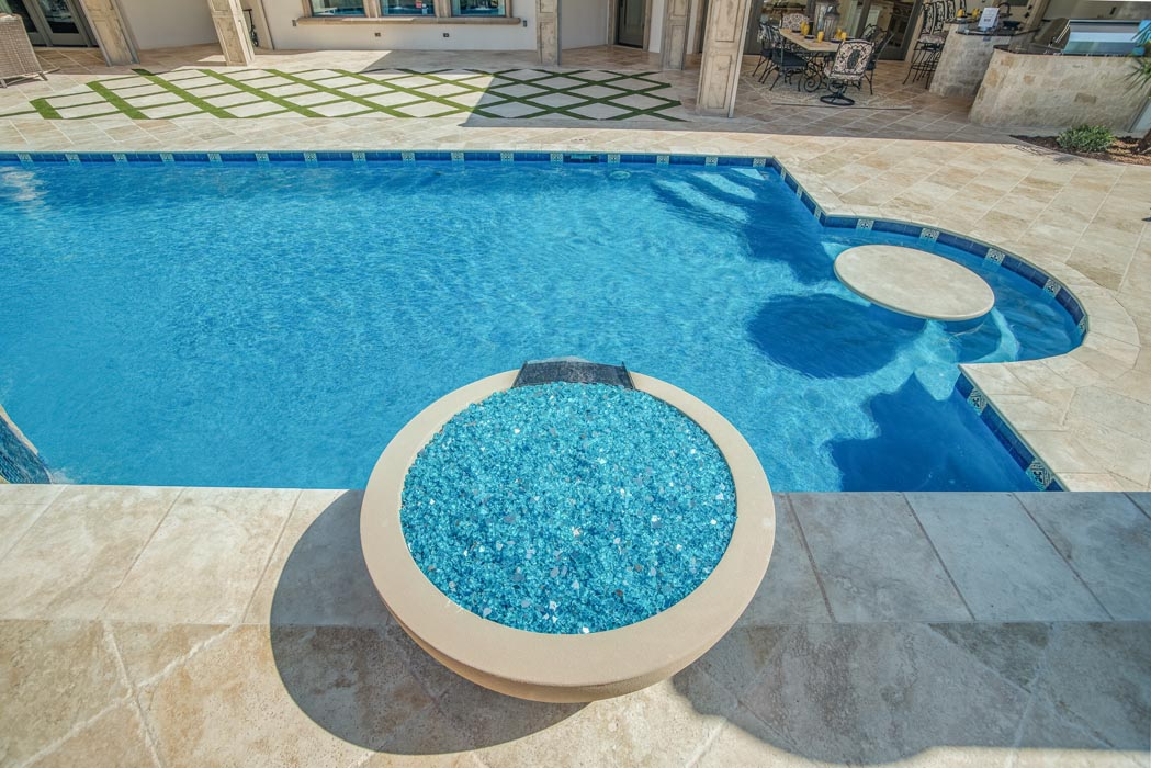 Pool with overflow hot tub in outdoor living area of custom home.