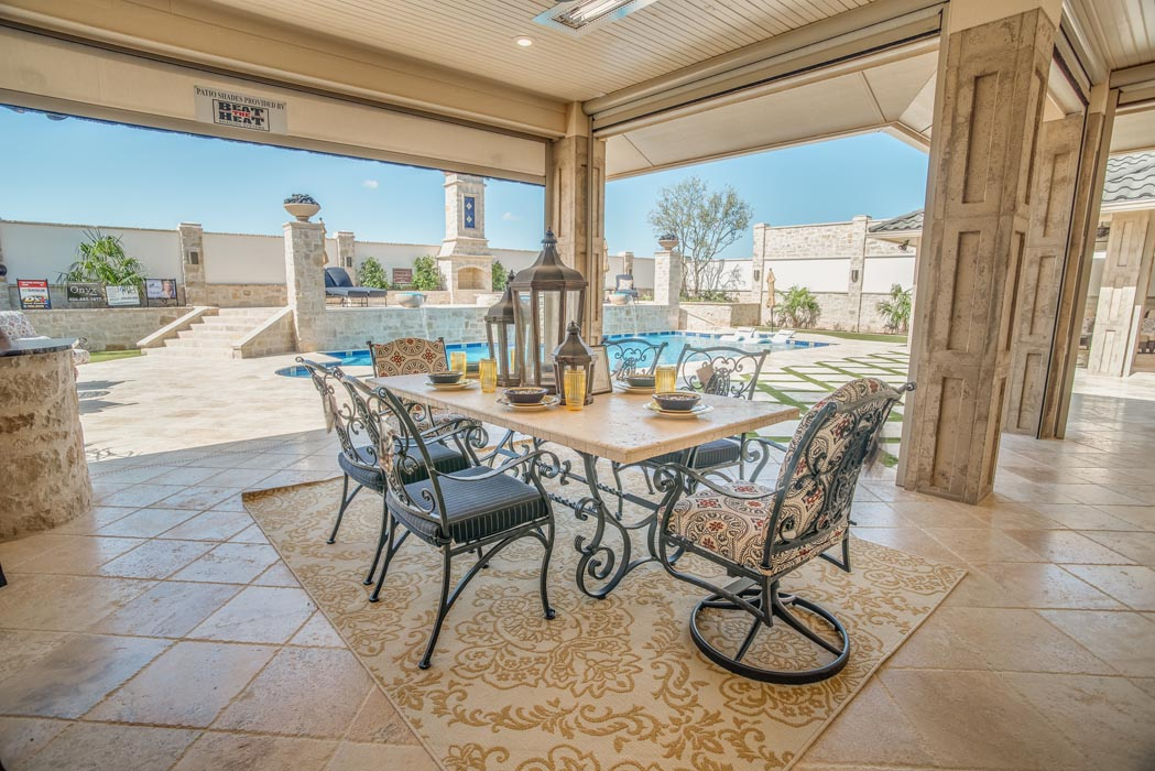Covered entertaining area, with views of pool, adjacent to custom home.