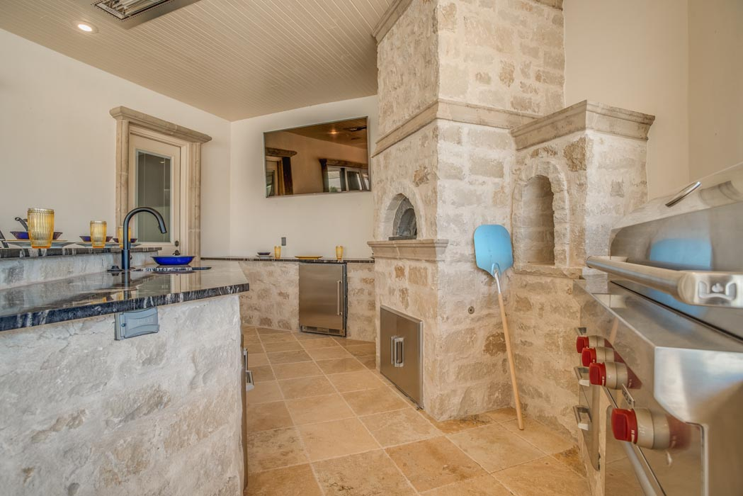 Outdoor kitchen, complete with pizza oven, in Austin stone, in patio area of custom home.