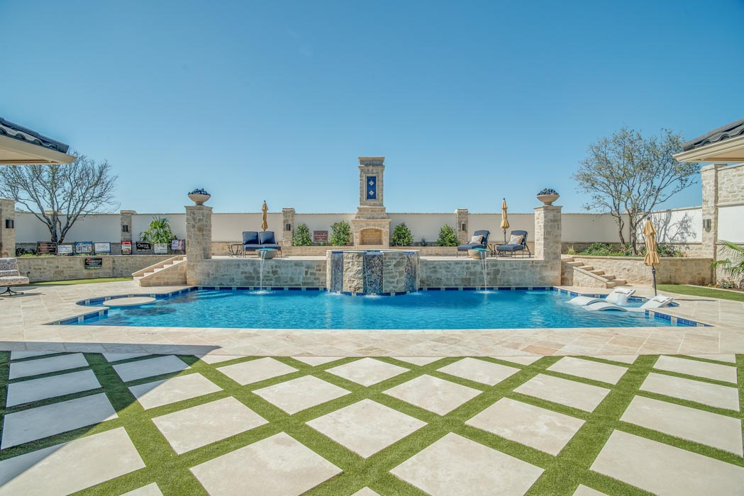 View of pool with special cross-hatch ground stone work, on the grounds of a custom home in Lubbock.
