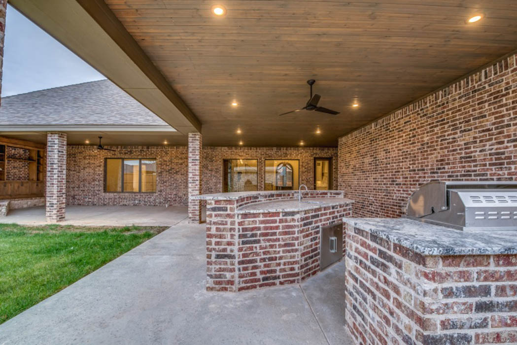 Long view of outdoor kitchen in patio of custom home in Lubbock.