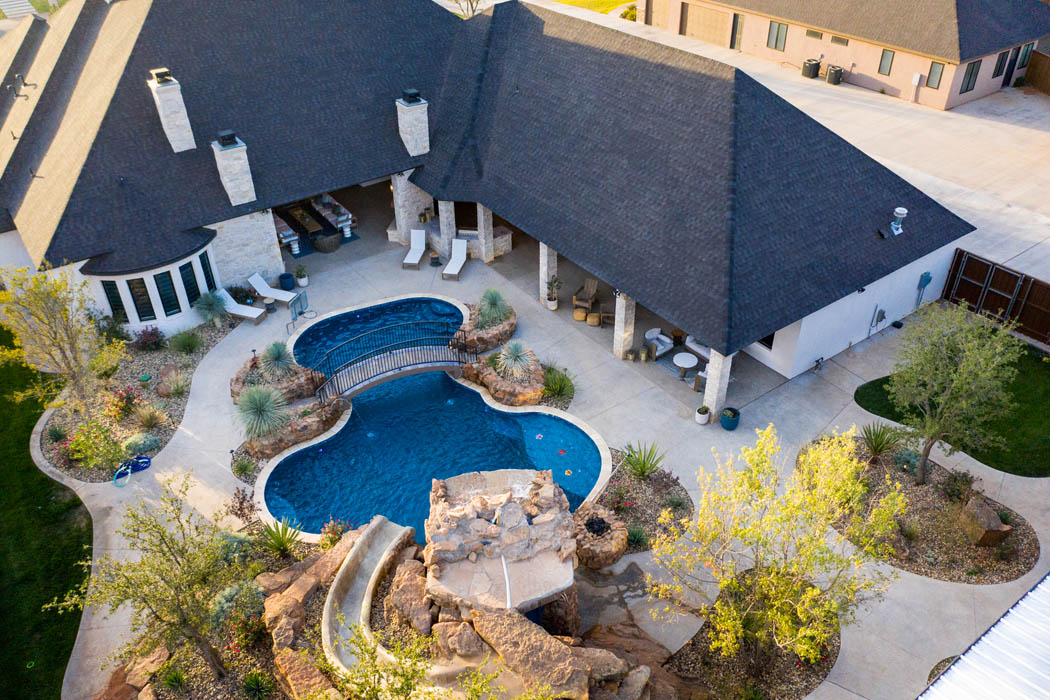 Amazing outdoor space in custom home feature beautiful pool with waterfall.