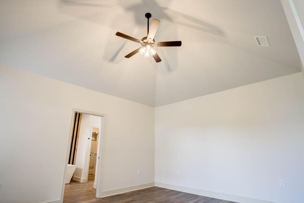 Spacious bedroom with vaulted ceiling & fan in new home for sale in Lubbock, Texas.