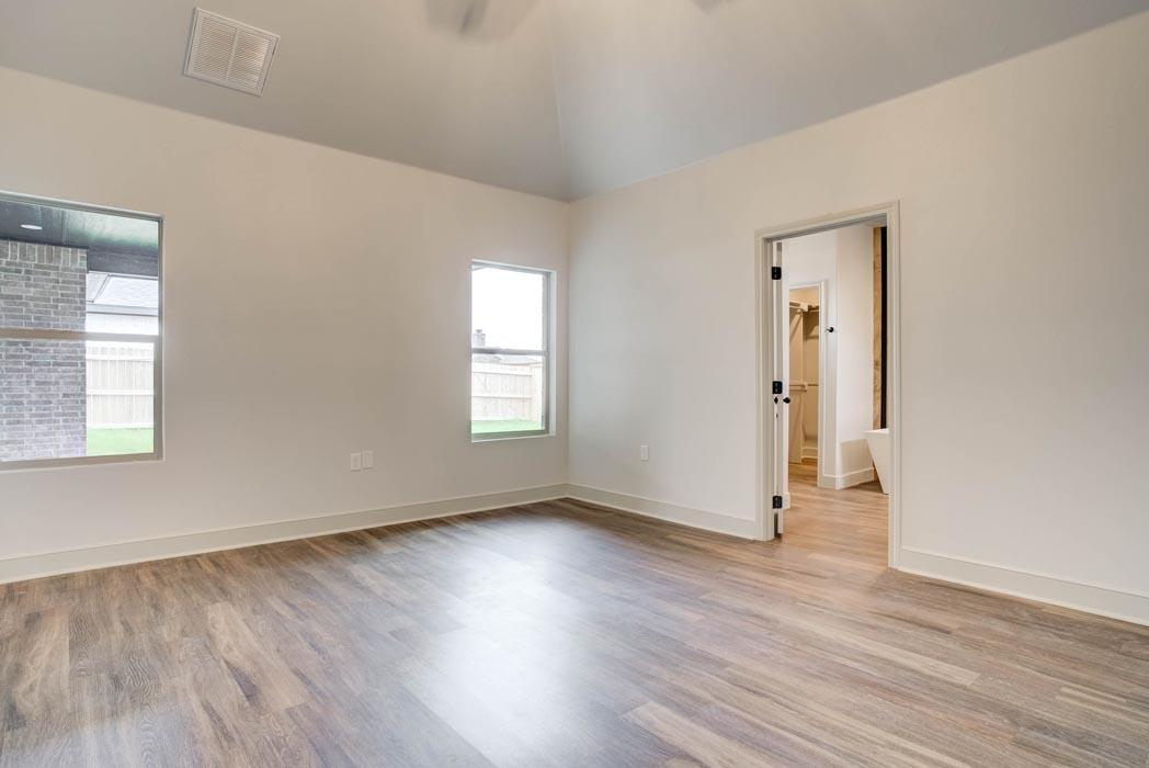 Spacious master bedroom with special ceiling in new home for sale.